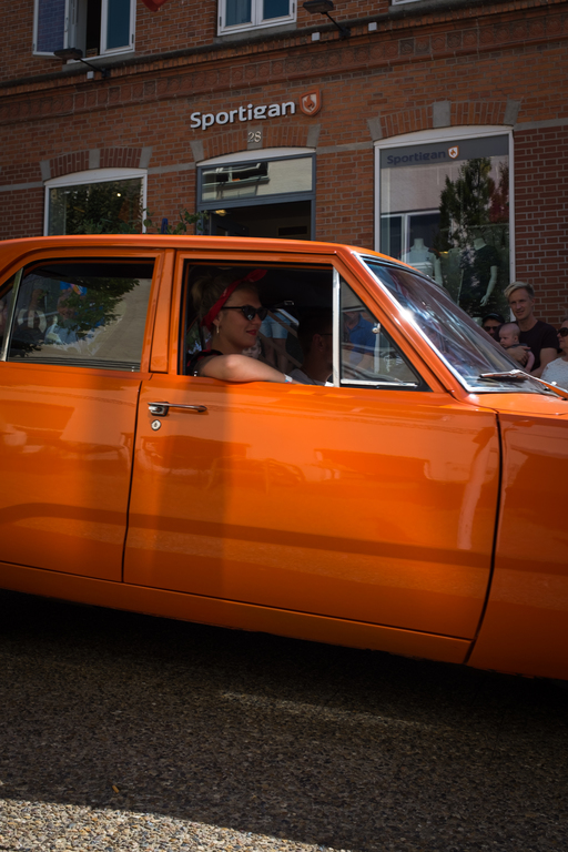 Woman smiling and sitting in a orange car