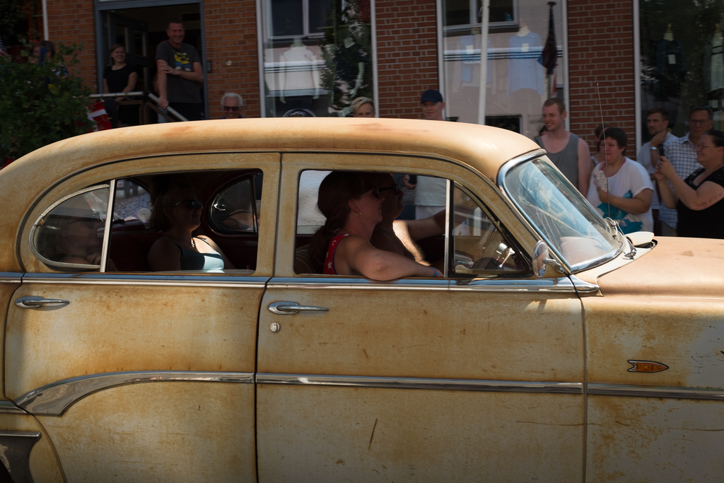Family cruising in a white rusty car